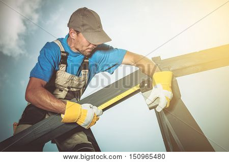 Wood Construction Job. Caucasian Construction Worker Measuring Wood Elements.