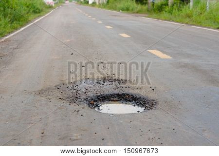 Damaged road with holes / pothole in the asphalt