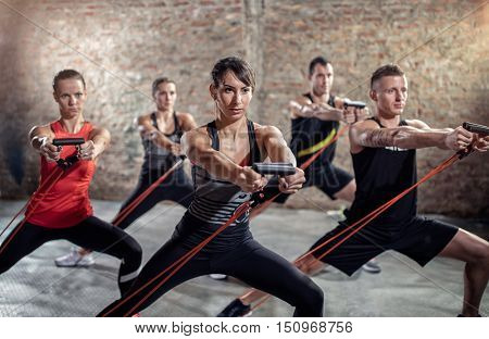 Powerful exercise with resistance band, group of young people doing workout together
