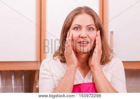 Surprise full disbelief housewife. Portrait of astonished woman looking suprised wearing pink apron standing in kitchen.