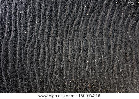 Black sand as background texture closeup photo