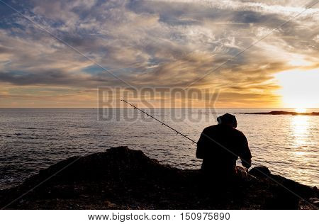 Silhouette of Fisherman holding a fishing pole at the beach at sunset in Southern California