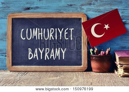 a chalkboard with the text Cumhuriyet Bayrami, the name for the Republic Day of Turkey in Turkish, a pot with pencils, some books and the flag of Turkey, on a wooden desk
