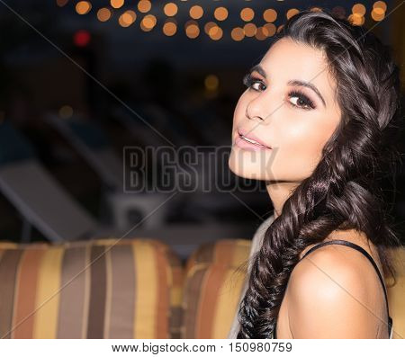 Beautiful young woman with braided hair sitting outside on patio at night time