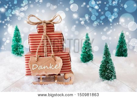 Sleigh Or Sled With Christmas Gifts Or Presents. Snowy Scenery With Snow And Trees. Blue Sparkling Background With Bokeh Effect. Label With German Text Danke Means Thank You