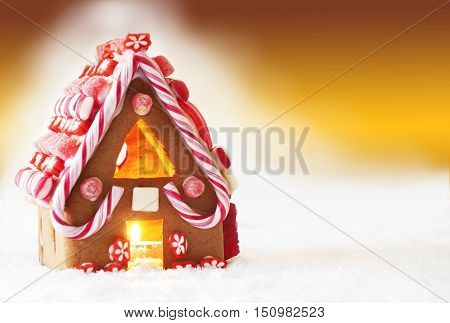 Gingerbread House In Snowy Scenery As Christmas Decoration. Candlelight For Romantic Atmosphere. Golden Background With Snow. Copy Space For Advertisement