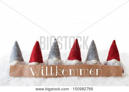 Label With German Text Willkommen Means Welcome. Christmas Greeting Card With Gnomes. Isolated White Background With Snow.