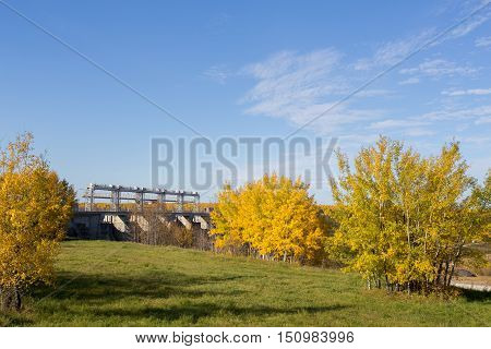 Hydro electric power station partially hidden by yellow autumn trees
