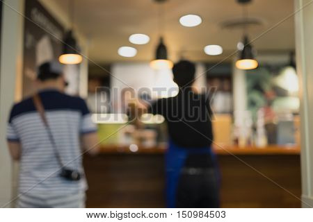 Blur restaurant with man ustomer and barista light lamp and ceiling as background/Blur restaurant customer barista