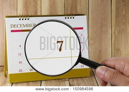 Magnifying glass in hand on calendar you can look seventh date of monthFocus number seven in DecemberConcept in business and meetings.