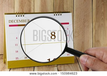 Magnifying glass in hand on calendar you can look eighth date of monthFocus number eight in DecemberConcept in business and meetings.
