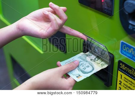 Hand inserting cash into a vending machine. selective focus.
