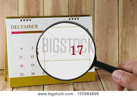 Magnifying glass in hand on calendar you can look Seventeenth date of monthFocus number seventeen in DecemberConcept in business and meetings.