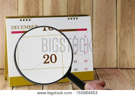Magnifying glass in hand on calendar you can look twentieth date of monthFocus number twenty in DecemberConcept in business and meetings.