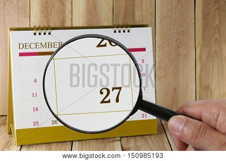 Magnifying glass in hand on calendar you can look Twenty-seven date of monthFocus number Twenty-seven in DecemberConcept in business and meetings.