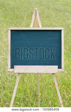 blank chalkboard with wooden easel on green field