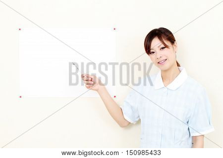 Young asian female nurse hand showing blank sign