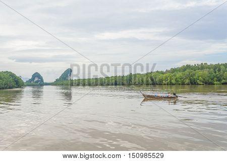 KRABI THAILAND - MAY 31 2016: Asian man rides his wooden long tail boat at Pak Nam river in Krabi Thailand.