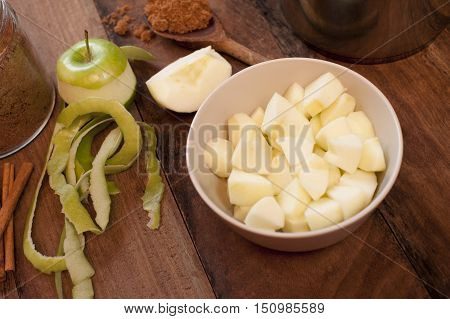Single partially peeled golden delicious apple beside chopped pieces in bowl on table