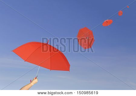Red umbrella in hand on blue sky backgroundumbrella blown by the wind in concept for management business idea.