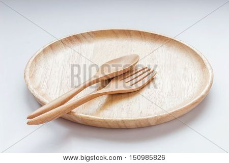 Close up empty flat wooden dish with spoon and fork made of wood as well.