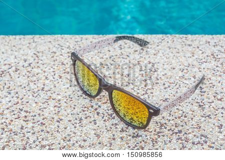 Cool sunglasses on the gravel poolside floor in sunny day.