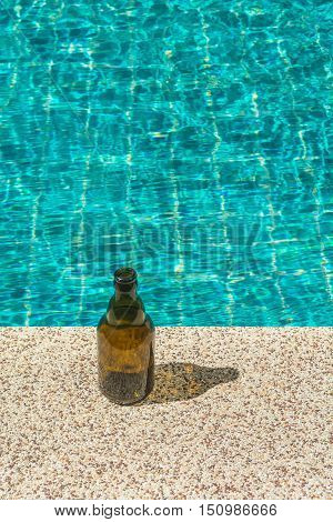 Short brown bottle next to the swimming pool in sunny day.