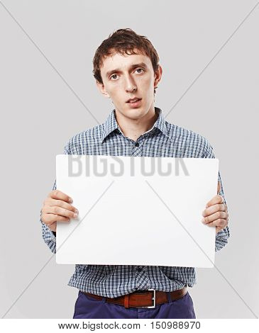 sad guy with a sheet of white paper in hands. young man holding a blank sheet of white paper for your text. looking at camera. mock-up. isolated on grey background