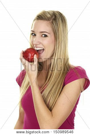 Beautiful Young Blonde Woman on a White Background.  She is about to take a bit of a red apple