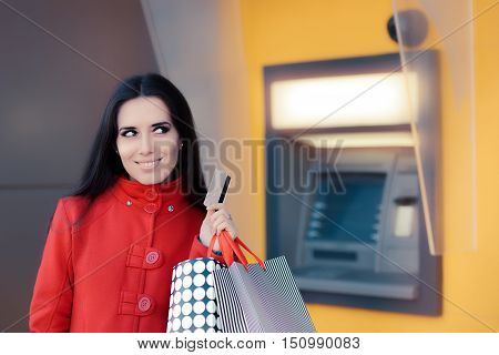 Happy Shopping Woman Holding Credit Card in front of an ATM