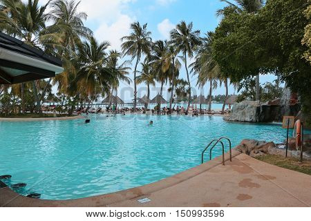 SUNISLAND, MALDIVES - FEBRUARY, 27, 2013: Swimmingpool on the beach with Palms