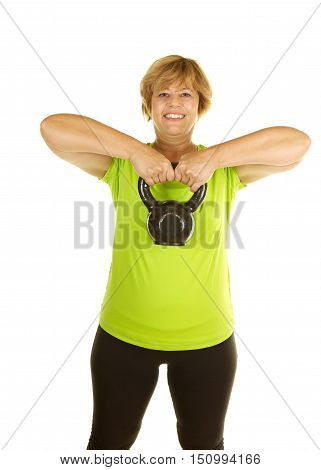 Middle Age Woman Exercising with Weights on a White Background.  She is using a kettle bell