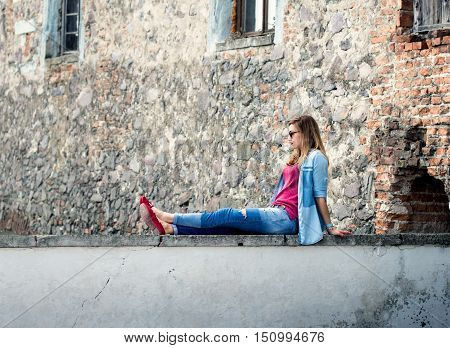 Young woman tourist relaxing on parapet on a sunny day copy space