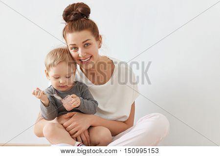 Beautiful Portrait Of Young Mother And Child Sitting Together On White Background. Happy Caucasian F