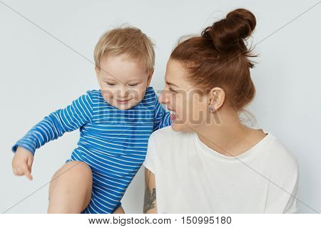 Funny Portrait Of Toddler And Happy Young Mother With Bunch Of Brown Hair Looking At Her Tomboy. You
