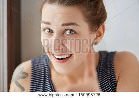 Esthetic close-up shot of young Caucasian woman showing joyful sincere happy feelings. Gorgeous and successful girl in stripped T-shirt with tattoo on shoulder smiling at camera with surprised look. poster