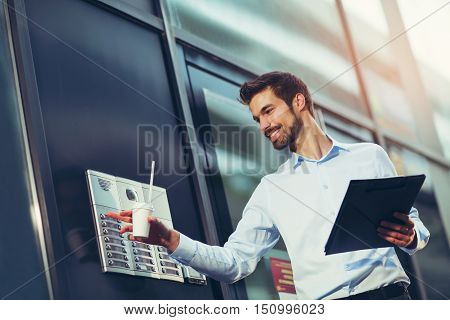 Portrait of a young happy businessman outside the office building enters the building