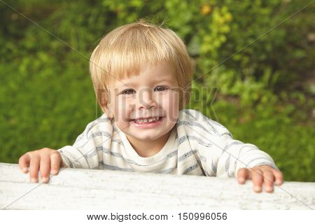 Beautiful Portrait Of Blond Smiling Child On Green Background. Little Kid Playing Outside In Summer