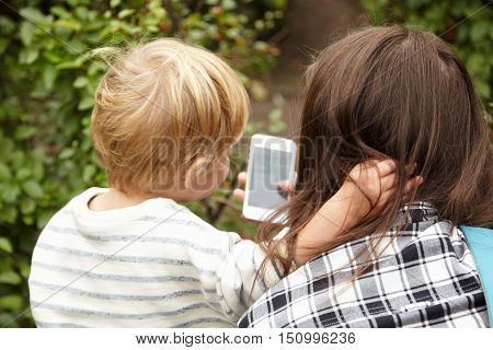Backside Portrait Of Mother And Son Outside. Blond Hair Of Little Boy Making Contrast With Brown Hai