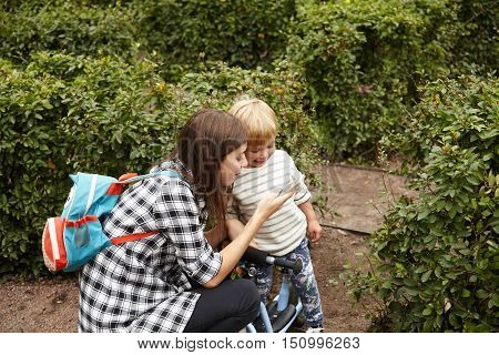 Beautiful Shot Of Caring Mother Walking With Her Son Outside. Young Caucasian Woman Showing Photos T