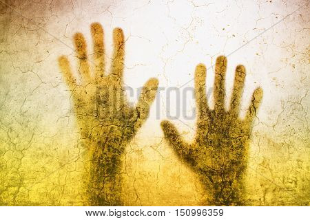 Back lit silhouette of trapped person hands behind matte glass useful as illustrative image for human trafficking prostitution imprisonment mental illness captivity depression.