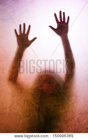 Trapped woman concept with back lit silhouette of hands behind matte glass useful as illustrative image for human trafficking prostitution imprisonment mental illness captivity depression.