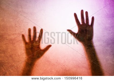 Captured female person concept with back lit silhouette of hands behind matte glass useful as illustrative image for human trafficking prostitution imprisonment mental illness depression.