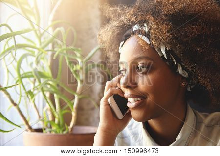 Close Up Portrait Of Attractive Stylish Dark-skinned Girl With Afro Hairstyle Wearing Bandana Talkin