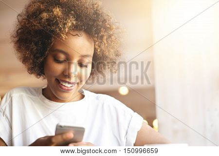Beautiful Stylish Young African Woman With Curly Hair Messaging Friends Using Mobile Phone, Looking