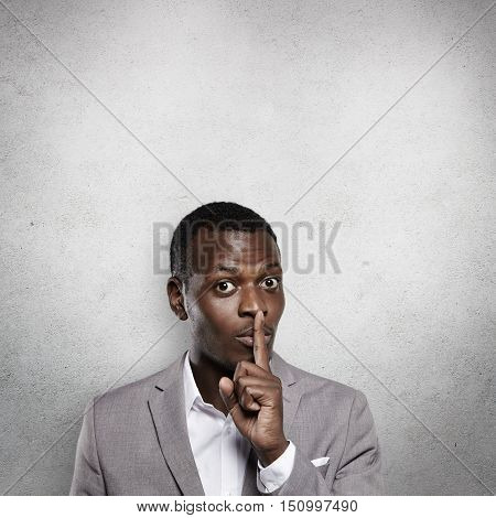 Studio Shot Of Handsome Dark-skinned Young Businessman In Formal Gray Suit Gesturing As If Asking No