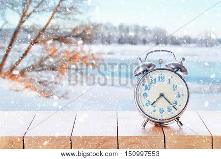 Vintage Retro Alarm Clock In Snowy Weather