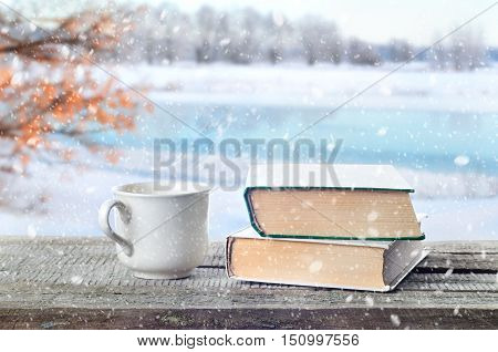 Cup hot coffee or tea cocoa chocolate and book outdoors on wooden table or bench in snowy weather on winter season background. Return to winter time. Pile of books and cup in nature.