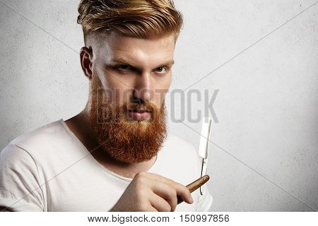 Headshot Of Attractive Professional Barber With Thick Red Beard And Mustache, Holding Razor. Young C