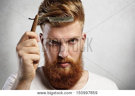 Good-looking Young Man With Red Beard Holding Barbershop Accessory. Caucasian Barber Demonstrating S